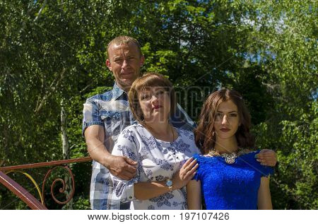 Parents with an adult slender daughter in the background of nature.