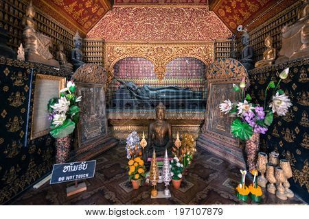 Wide angle picture of reclined Buddha and other images inside Wat Xieng Thong Buddhist temple located in the city Luang Prabang Laos.