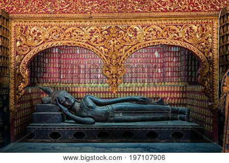 Reclined Buddha and golden carving inside Wat Xieng Thong Buddhist temple located in the city Luang Prabang Laos.