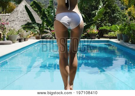 Back view of female back buttocks and legs staiding in front of swimming pool in tropics