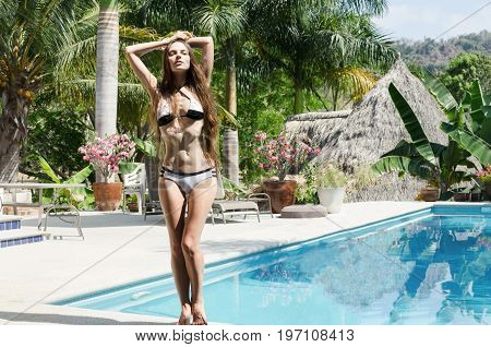 Beautiful young woman enjoying the sun at the edge of swimming pool