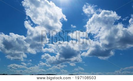 Sunlit clouds, blue sky, sunny summer day