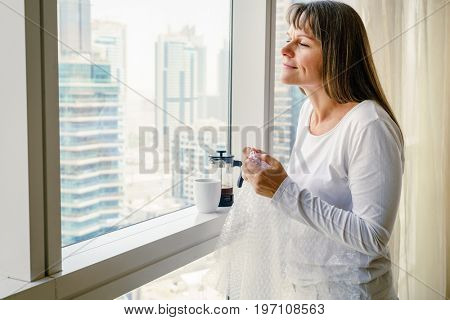 Mature woman by the window is releasing stress by popping bubble wrap