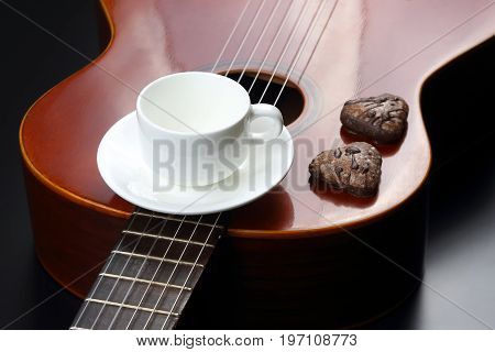 empty white coffee Cup and cookies on acoustic guitar