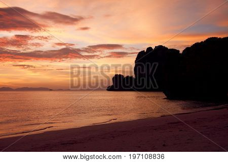 Black silhouette of rocks at the sandy beach during stunning sunset