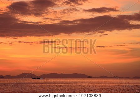 Longtail boat silhouette at the sea during stunning sunset