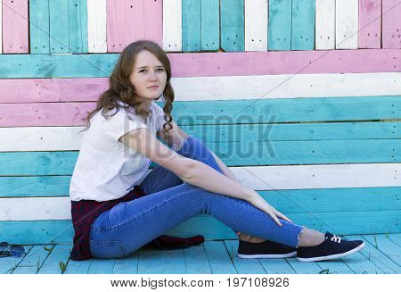 A young girl with a smile in jeans sneakers a white T-shirt and sunglasses in her hair sits on colorful boards