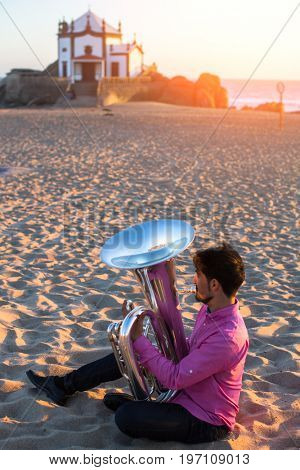 Young man playing the trumpet on the sea coast. Tuba instrument. In the background is the Chapel Senhor da Pedra at Miramar Beach, Atlantic ocean, Porto, Portugal.