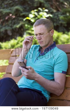 Middle-aged man wearing glasses on his nose close-up reading a message on a smartphone sitting on a bench in a city park outdoors.