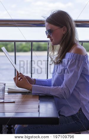 Young girl sitting at a table in a cafe on the waterfront in jeans and a shirt reading a menu in summer outdoors closeup