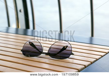 Sunglasses on the wooden table of a summer cafe