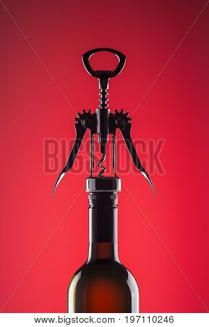 A bottle of wine with a stylish corkscrew for opening on a red background.