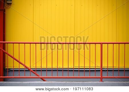 A colorful red railing in front of the yellow checkered facade of a shopping center.