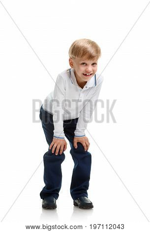 Happy smiling young schoolboy crouching on white background
