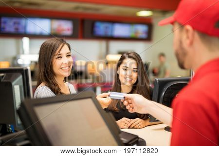 Point of view of a male worker getting a credit card from a pair of friends at the movie theater