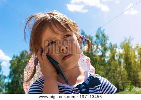 Little Girl Looking Up And Speaking By Cell Phone,