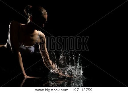 Young beautiful blonde with bunch hair style wearing white top enjoying water splashes in dark studio