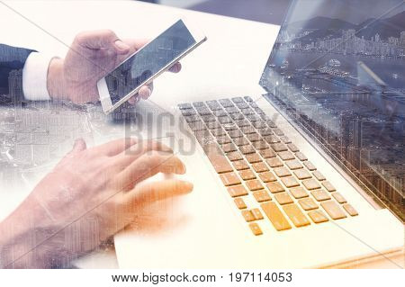 Double exposure of success businessman working in office with digital tablet laptop computer with Hongkong building and smart phone.