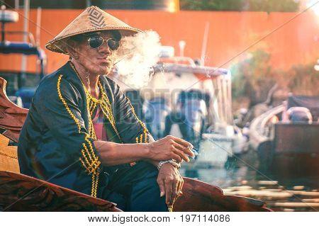 Semporna,Sabah-Apr 22,2017:Portrait of a Sea Bajau man smokes cigarette with traditional costume during Regata Lepa Lepa in Semporna,Sabah,Malaysia.