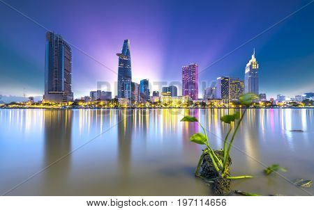 Ho Chi Minh City, Vietnam - July 9, 2017: Riverside City sunset end of day brighter sparkling skyscrapers coal along river, this is a symbol economic development country in Ho Chi Minh City, Vietnam