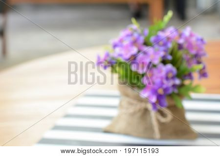 Small purple flowers in jute bag on the table - can be used as blurred background without focus