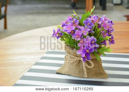 Purple flowers in small jute bag on the table