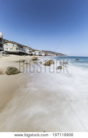 Oceanfront homes with motion blur water at Carbon Beach in Malibu, California.