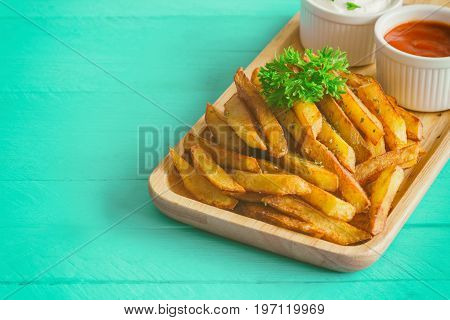 Homemade french fries serve with ketchup and sour cream or mayonnaise. Golden brown crispy french fries sprinkle with salt and oregano on wood plate for snack or appetizer. French fries on wood table.