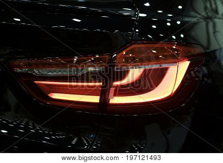 Red Rear light on a modern black car with reflection. The Closeup Back Red Tail light car
