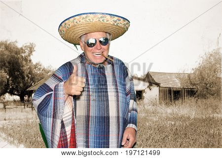 a man wears a sombrero and a serape while posing in a photo booth against a green screen or chroma key background