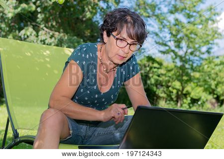 Modern casual woman sitting at garden with a laptop