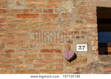 Road sign on a house reading the number thirty seven made out of metalic digits on a marble base. Sign is situated in the lower right hand part of the photo next to a purple ceramic heart