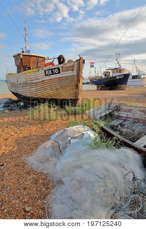 HASTINGS, UK - JULY 21, 2017: Beach launched fishing boats at sunset with white fishing nets in the foreground