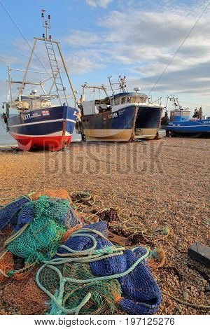 HASTINGS, UK - JULY 21, 2017: Beach launched fishing boats at sunset with colorful fishing nets in the foreground