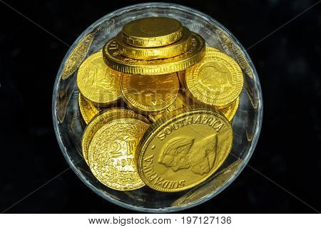 a glass of (chocolate candies) gold coins symbolizing growing wealth and fortune