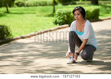 Portrait of cheerful Asian woman stopping to tie shoes during jogging workout in park on sunny day
