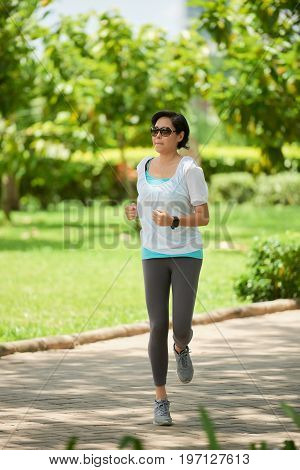 Portrait of healthy Asian woman running in park on sunny day
