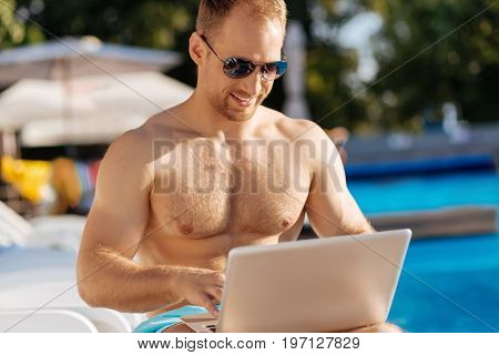 Pleasant pastime. Upbeat young man in sunglasses relaxing near a swimming pool and chatting with someone on his laptop while smiling