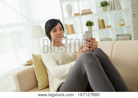 Portrait of smiling Asian woman using smartphone at home lying on comfortable sofa and reading text messages