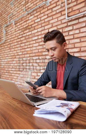 Portrait of young Asian man working in cafe, using smartphone and laptop sitting against brick wall