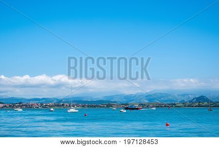 Panoramic views of mountains sea and white sailboats in front of the city of Santander. Cantabria Spain.