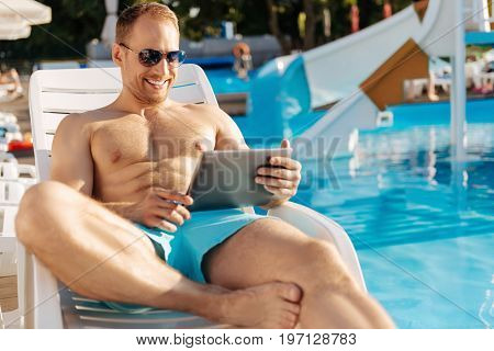 Makes me smile. Smiling athletic young man lying on a chaise longue near a swimming pool and watching a video online while smiling happily