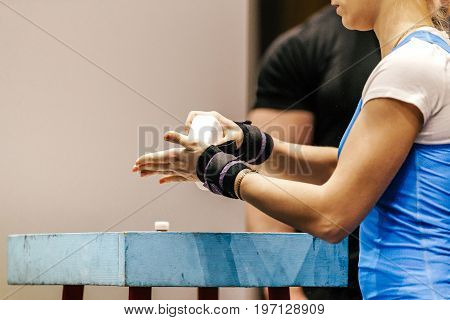 female powerlifter puts hands in chalk wrist wraps powerlifting