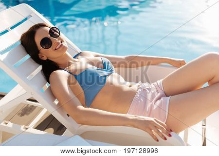 Good weekend. Attractive young woman in a blue bra and pink shorts lying on a chaise longue near a swimming pool and sunbathing while smiling at the camera pleasantly
