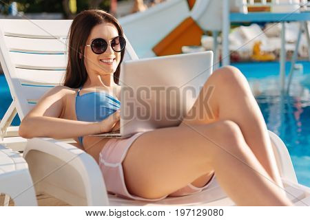 Important discussions. Upbeat curvy woman lying on a chaise longue and exchanging messages with her best friend in social networks while smiling pleasantly