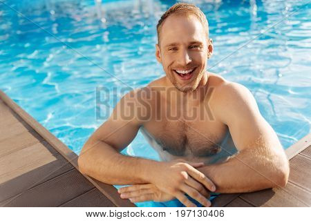 Happy to refresh. Overjoyed young man standing chest-deep in the swimming pool water, resting his elbows on the pool sides and smiling broadly at the camera