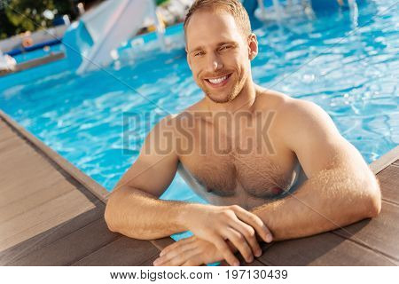 Enjoying freshness. Cheerful well-built young man standing chest-deep in the swimming pool water and smiling at the camera pleasantly
