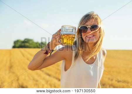 Happy girl holding beer glass in a big wheat-field.