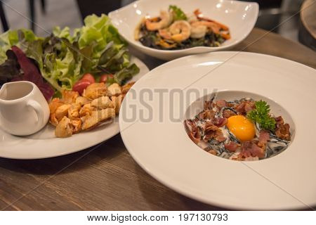 A italian food carbonara spaghetti with egg salad salmon and shrimp spaghetti.
