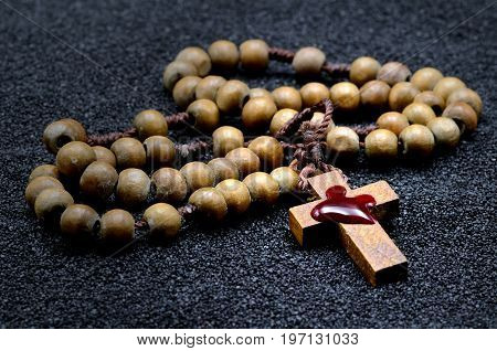 Rosary with blood on a black sand
